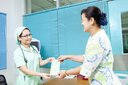 pamphlet: Nurse handing pamphlet to a patient Stock Photo