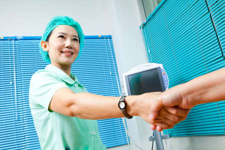 Healthcare professional and patient shaking hands photo