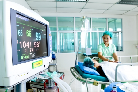 Close up of a medical monitor with patient and nurse in the background