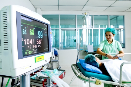 Close up of a medical monitor with patient and nurse in the background photo