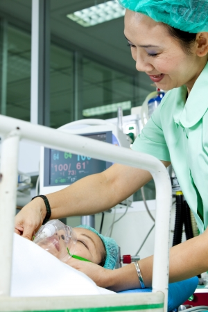 Nurse adjusting oxygen mask on a patient photo