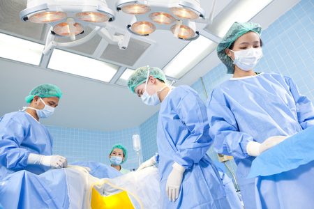 operation gown: Surgeons and nurses in an operating room