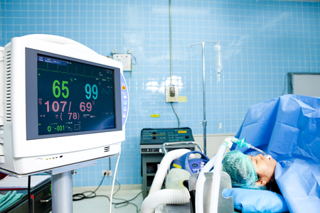 Medical monitor with sedated patient in the background photo