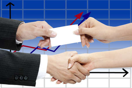 Business people exchanging business card and shaking hands