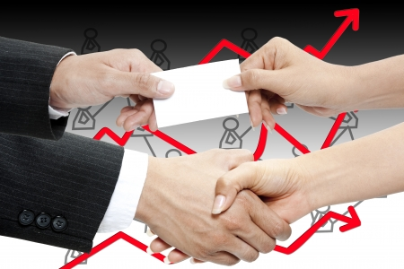 Business people exchanging business card and shaking hands photo