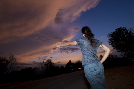 A woman trying to hitchhike at dusk photo
