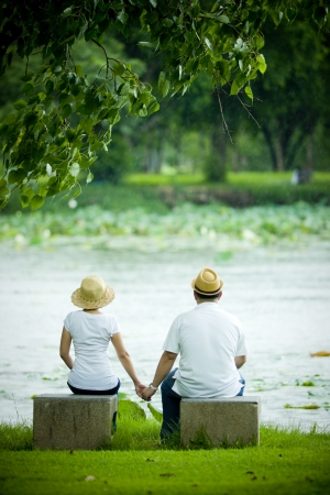 A couple holding hands by a lakeside Foto de archivo