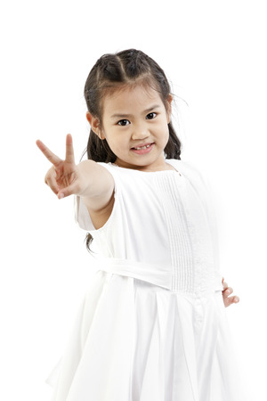 A young Asian girl doing a hand gesture Foto de archivo