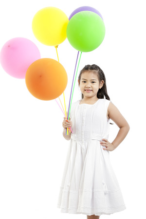 A young Asian girl holding colourful balloons Stock Photo - 25230343