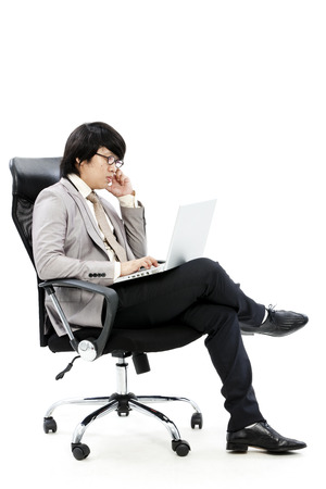 Asian man sitting on the chair with his laptop photo
