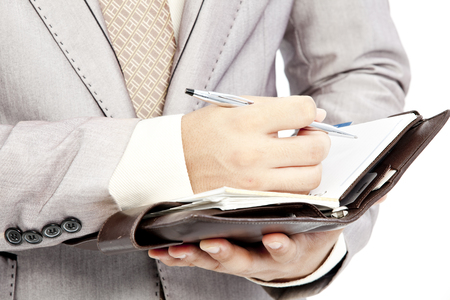 Close up of businessman writing on his notebook photo