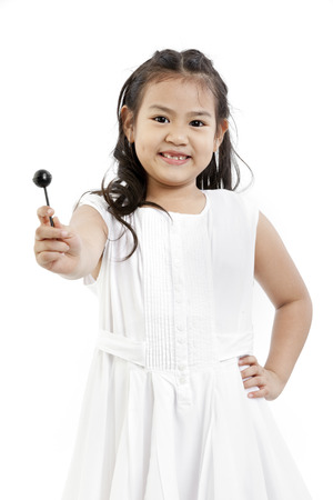Potrait of a happy girl posing with her lollipop photo
