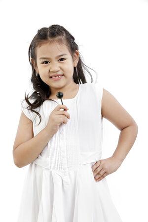 Portrait of a happy girl holding a lollipop  photo