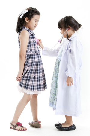 Two girls playing the roles of doctor and patient photo