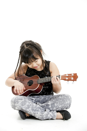 Girl strumming guitar while sitting cross legged on floor photo