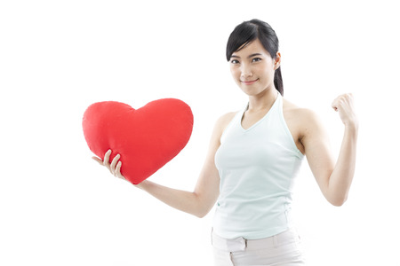 Young woman holding a heart shape cushion and showing fist photo