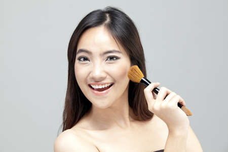 Young woman applying blusher on cheek and smiling photo