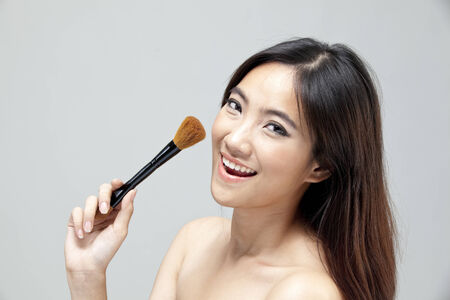 Young woman holding makeup brush and smiling photo