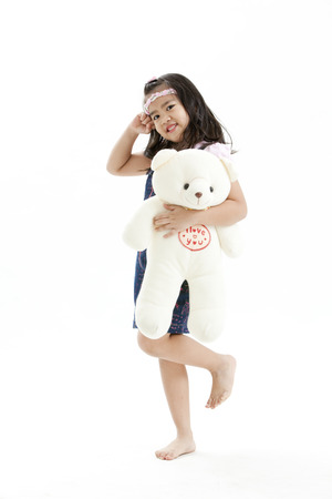 Girl posing in casual clothings while holding a stuff toy photo
