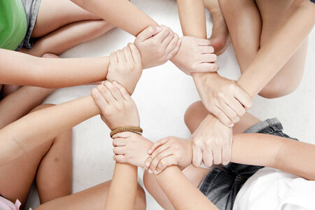 linking together: Linking of hands on white background Stock Photo