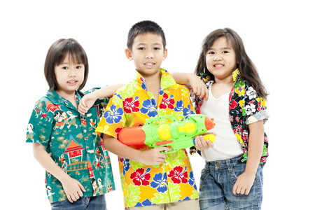Boy holding a plastic toy gun standing with two girls beside him Stock Photo - 28663375