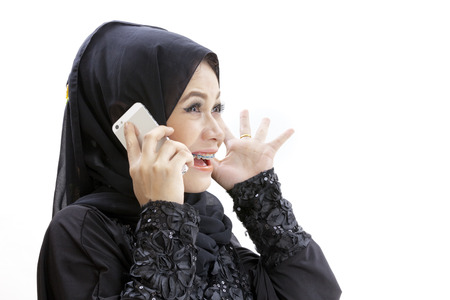 exclaiming: Woman wearing a hijab and dressed in malay attire while talking on the phone Stock Photo