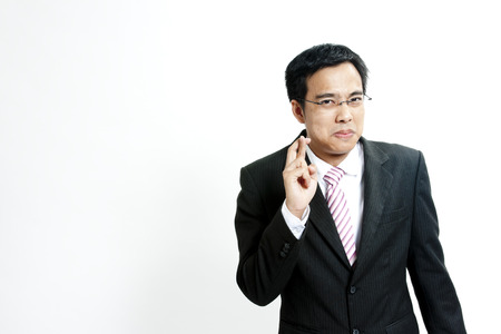 Businessman with fingers crossed photo