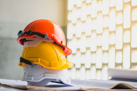 white, yellow and orange hard safety, helmet hat for safety project of workman or engineer on desk and construction plans with on blueprints