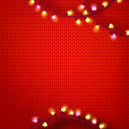 Red kniting background with garland lights .