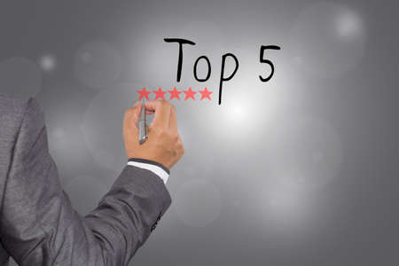 best travel destinations: Businessman writing Top 5 with pen on visual screen. Business, technology, internet concept.