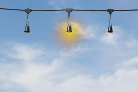 electric bulb: light bulb on electric cable line with sky background