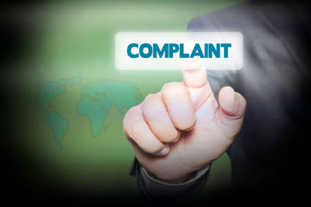 complaint: Hand pressing Complaint on virtual screen. business concept. Stock Photo