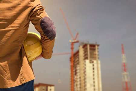 Worker or engineer holding in hands helmet for workers security on background of new highrise apartment buildings and construction cranes on background.