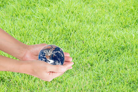 Hand holding the world against blur of green background, human hands with healthy world concept, love and safe conception. Editorial