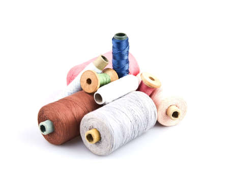 Several cones of thread of different colors on a white background