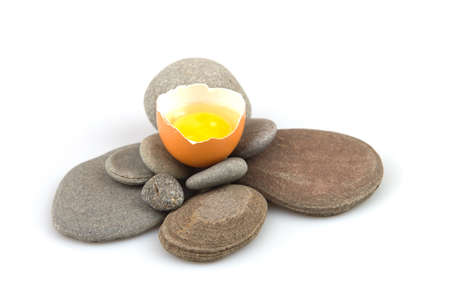 Raw, beaten egg on sea pebbles on a white background