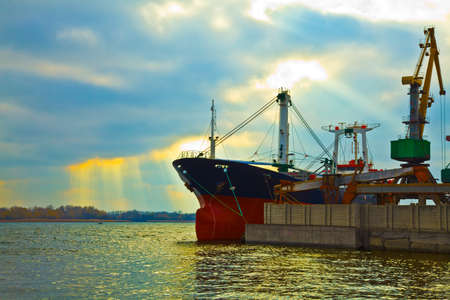 Cargo crane loads a cargo vessel at the port Stock Photo