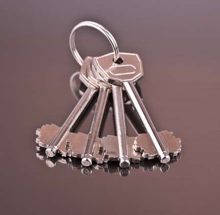 Four keys, shine, reflection and gray background from aluminum