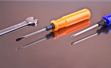 Two screwdrivers and a wrench on a gray background with reflection Stock Photo