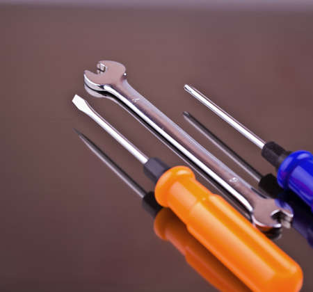 Wrench and two screwdrivers on a gray background with reflection Stock Photo