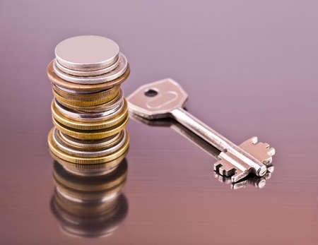Stack of coins and a key on a gray background with reflection