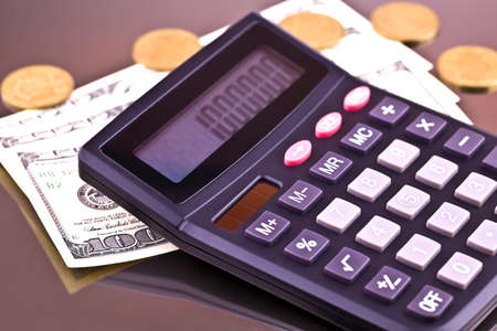 Money, coins and the calculator on a gray background from aluminum Stock Photo