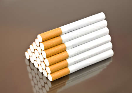 21 cigarettes as a pyramid on a gray background from aluminum Stock Photo