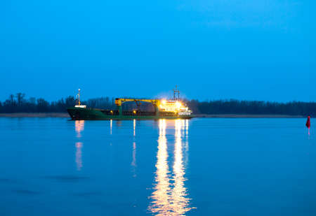 Cargo ship on the river in the evening