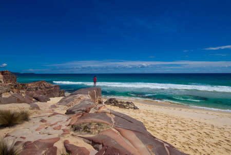 tourist with backpacks on a large stone and enjoying Sea View  Ben Boyd national park, Australia photo