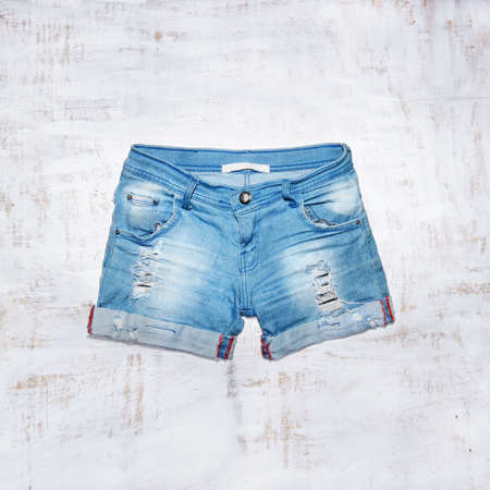 Jeans shorts in wood background Imagens