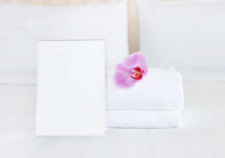 offer: clean towel and empty blank for your text on the bed Stock Photo