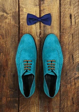 lazo regalo: zapatos masculinos y pajarita sobre un fondo de madera marrón