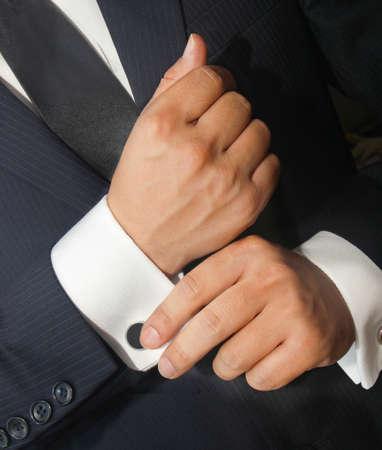 cufflinks: A man in a black suit straightens his cufflinks