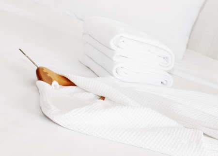 white bathrobe on the bed